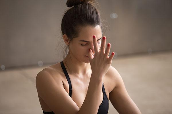 Young attractive woman making nadi shodhana pranayama, grey stud